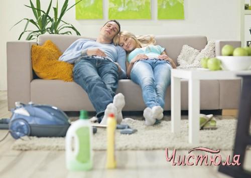 Мужчина и женщина сидят на диване после уборки