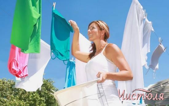Женщина развеивает белье на веревке